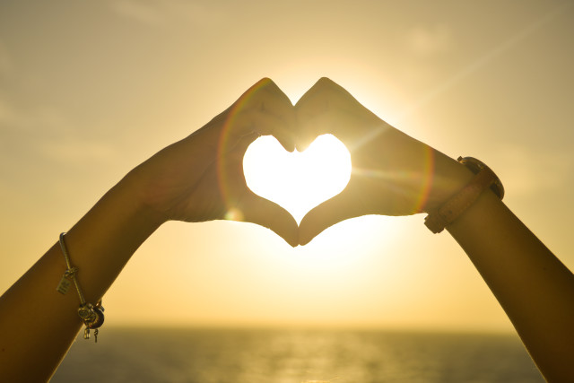 Love Heart Made With Hands At Sunset_