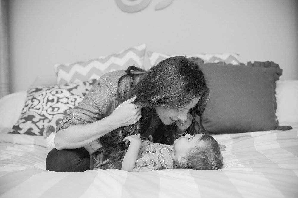 Mom holding hair back as she leans down to kiss child on nose
