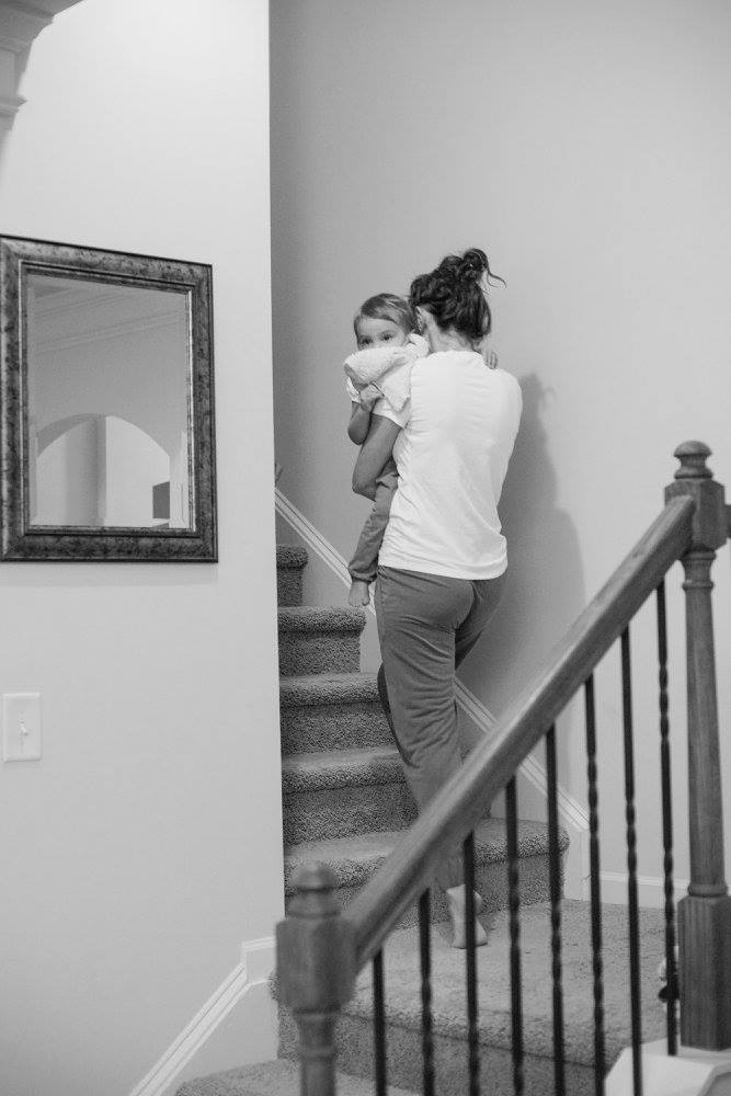 Mom Carrying Child Up the Stairs