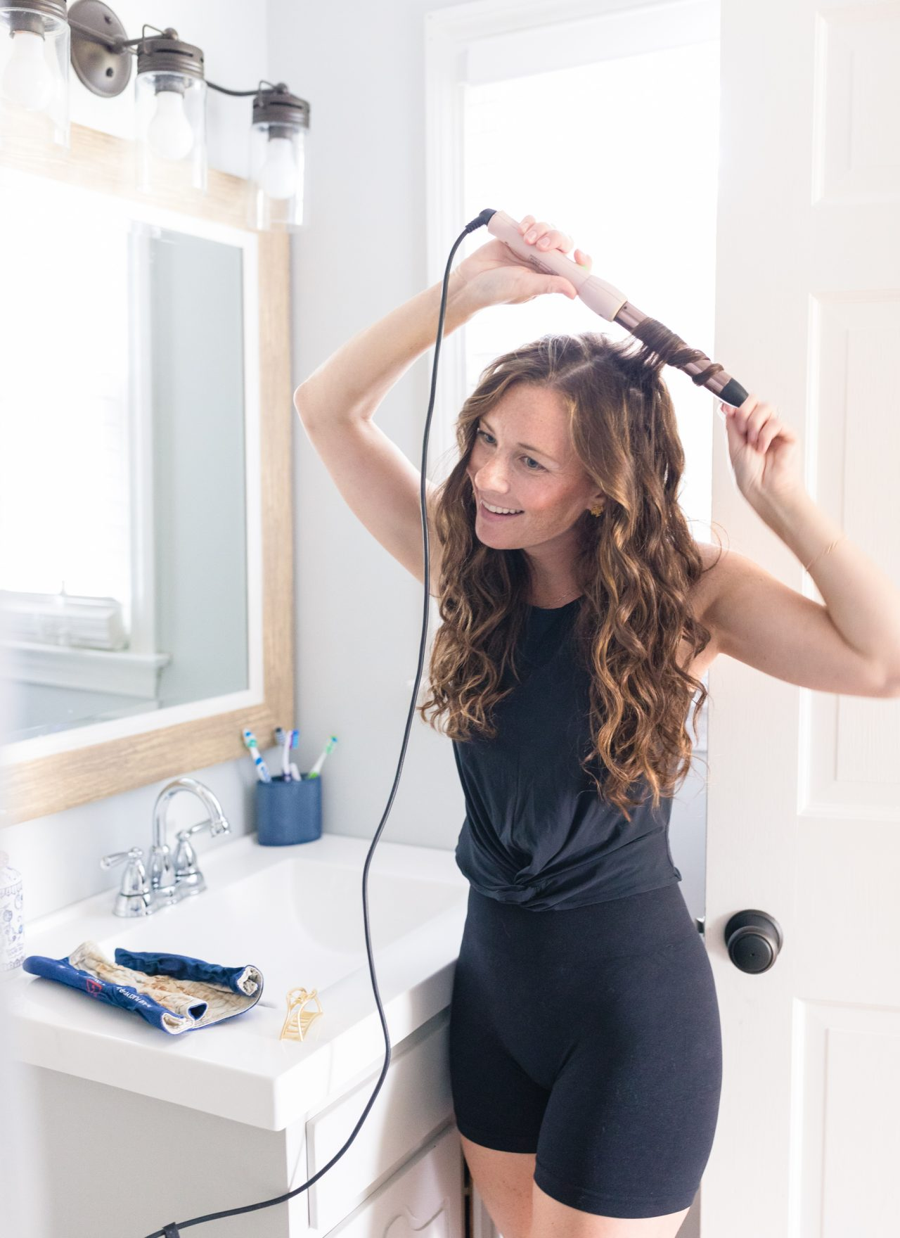 woman curling hair with wand