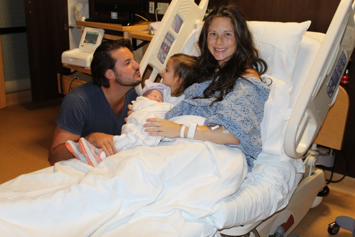 Dad kissing new baby girl and daughter and mom in hospital bed