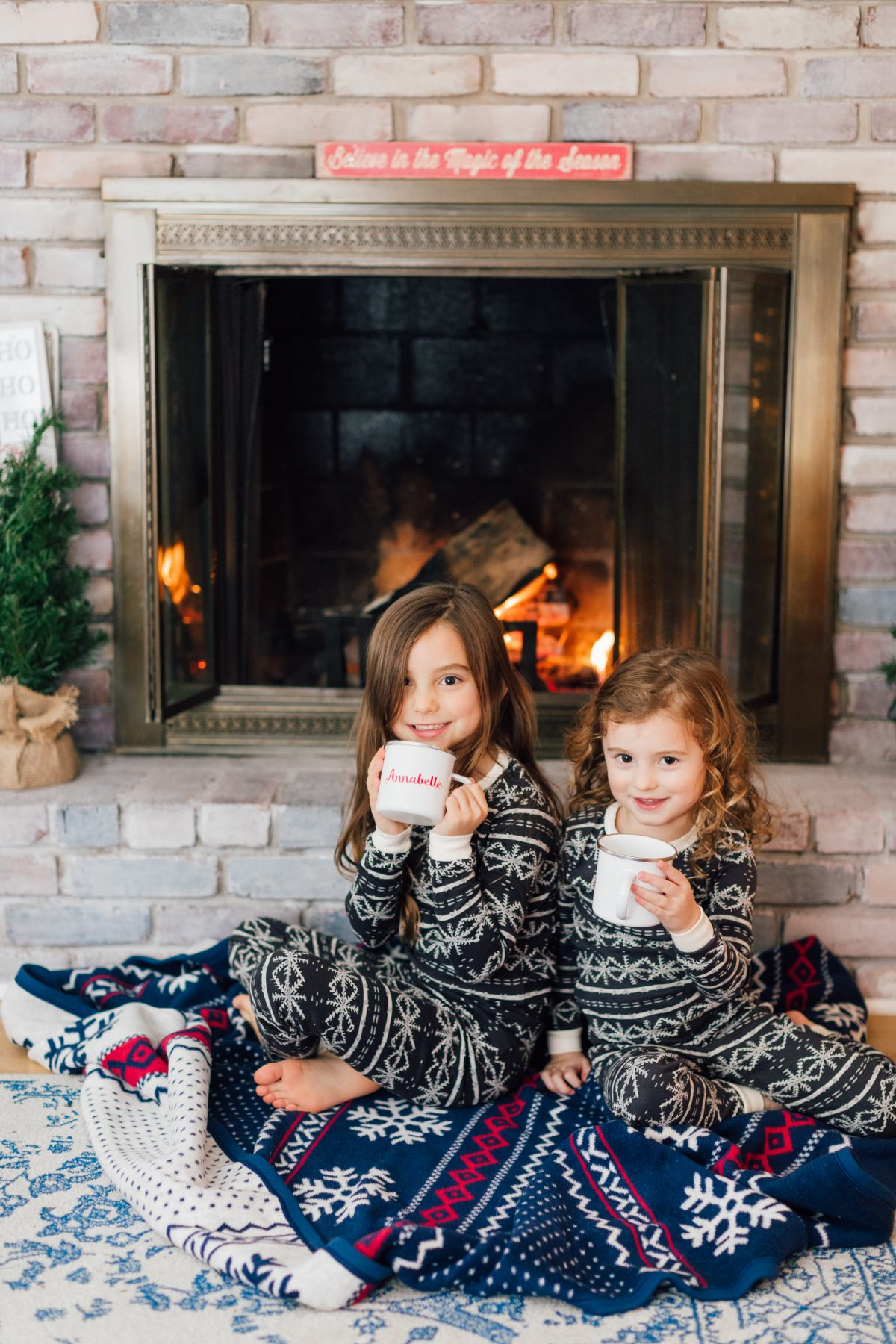 Holiday Family Photo Inspiration - Little Girls Sipping Hot Cocoa by the Fireplace with Christmas Pajamas and Chappy Wrap Blanket