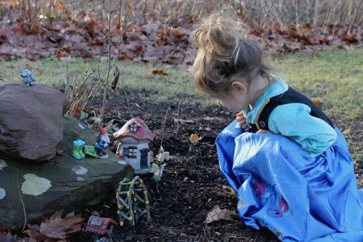 Little girl looking at a fairy garden