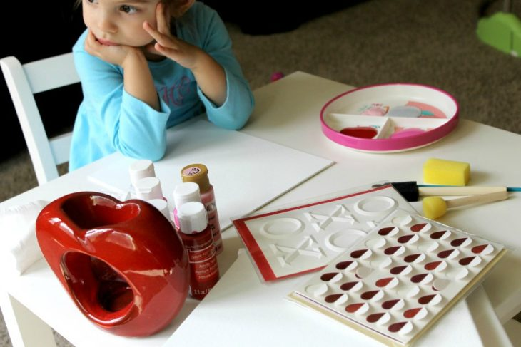little girl sitting with valentine's decor and craft supplies