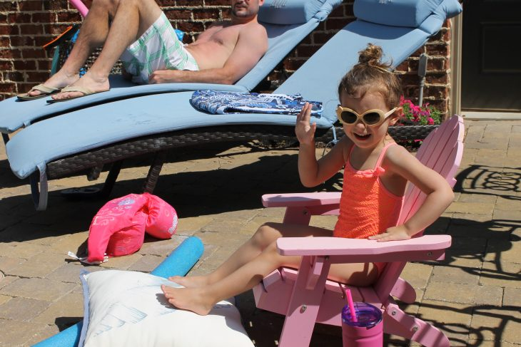Little girl in sunglasses smiling in the sun
