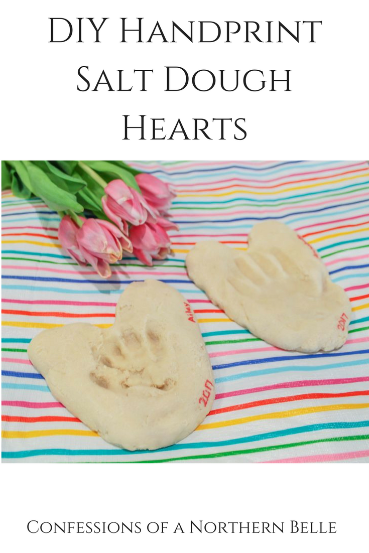 Handprints on Salt Dough Hearts, Resting on a Striped Tablecloth with Tulips in the top corner