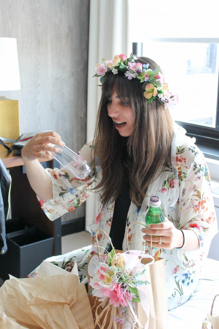 bride wearing flower crown holding champagne flute
