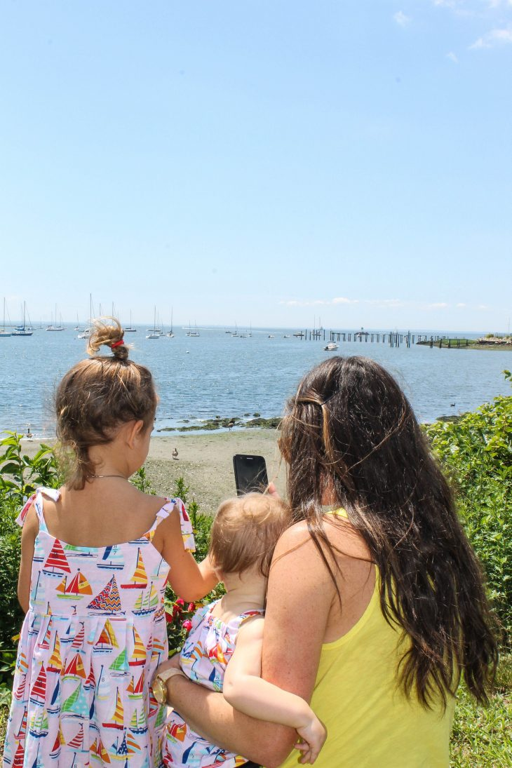 Mom and Daughters on bluff at beach looking at phone