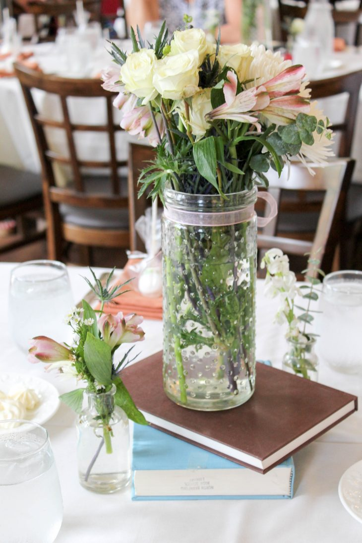 Fresh flowers in glass vase on vintage books centerpiece
