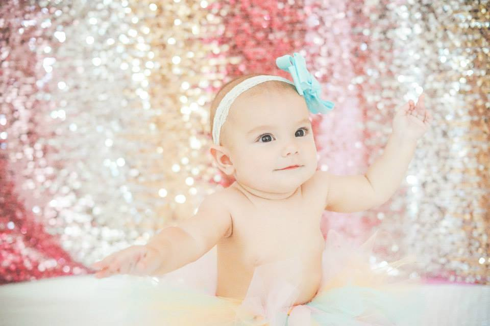 Baby in tutu sitting in front of a glitter wall