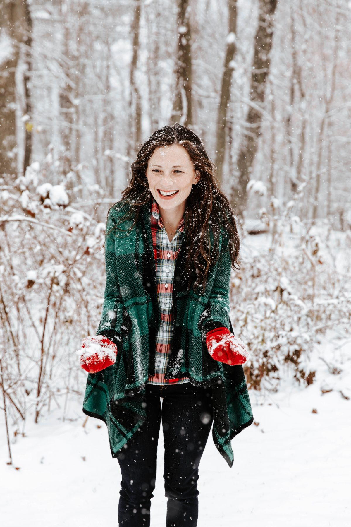woman smiling and catching snowflakes in the middle of a snowstorm wearing a green and black plaid shawl over a red plaid shirt