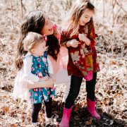 Woman laughing with two young girls wearing spring outfits