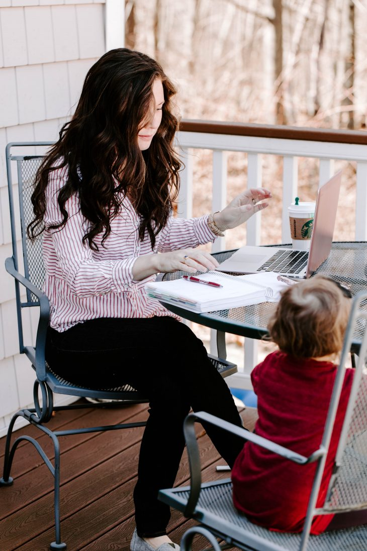 Woman working at laptop with child sitting beside her
