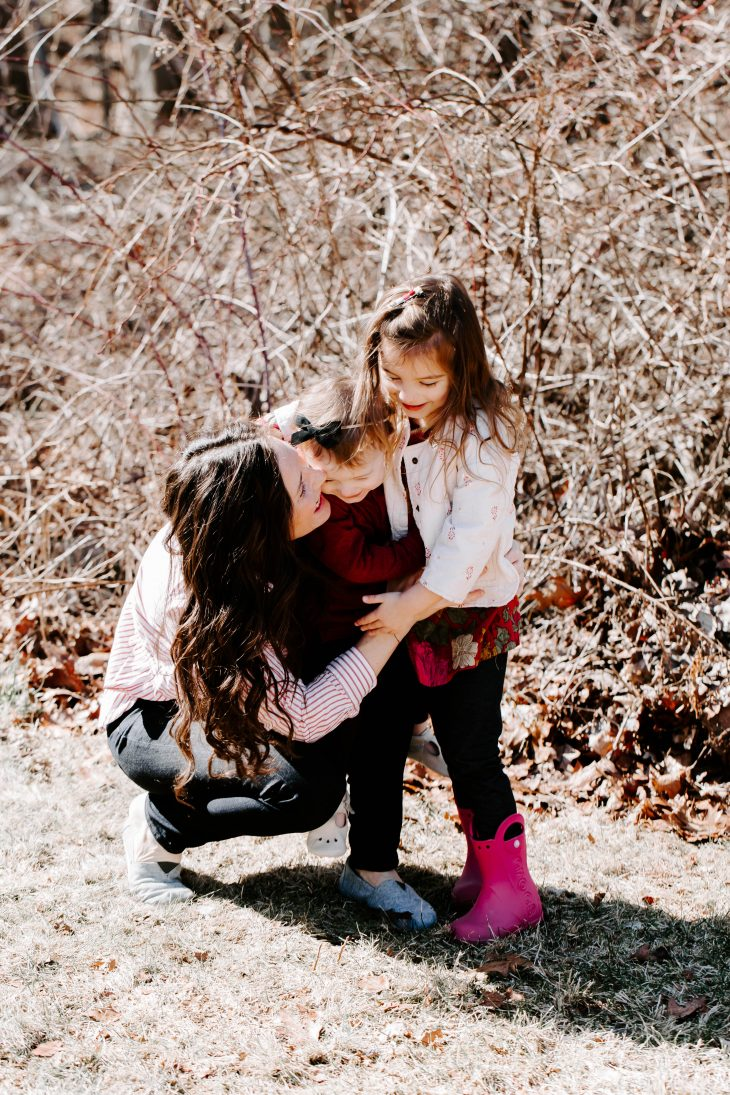 woman hugging two children
