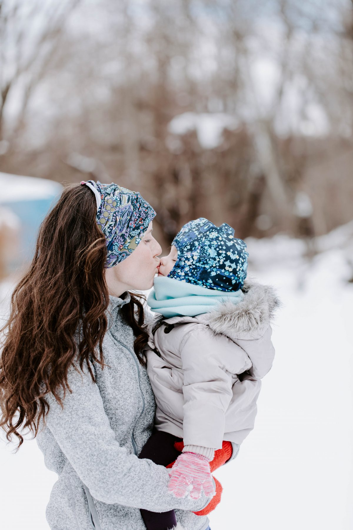 Mom wearing snow headband kissing baby wearing snow hat