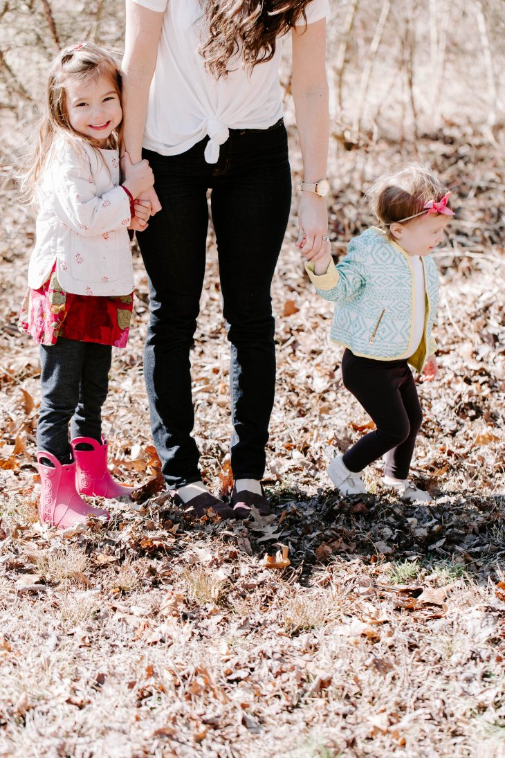 Little girls standing beside Mom's legs