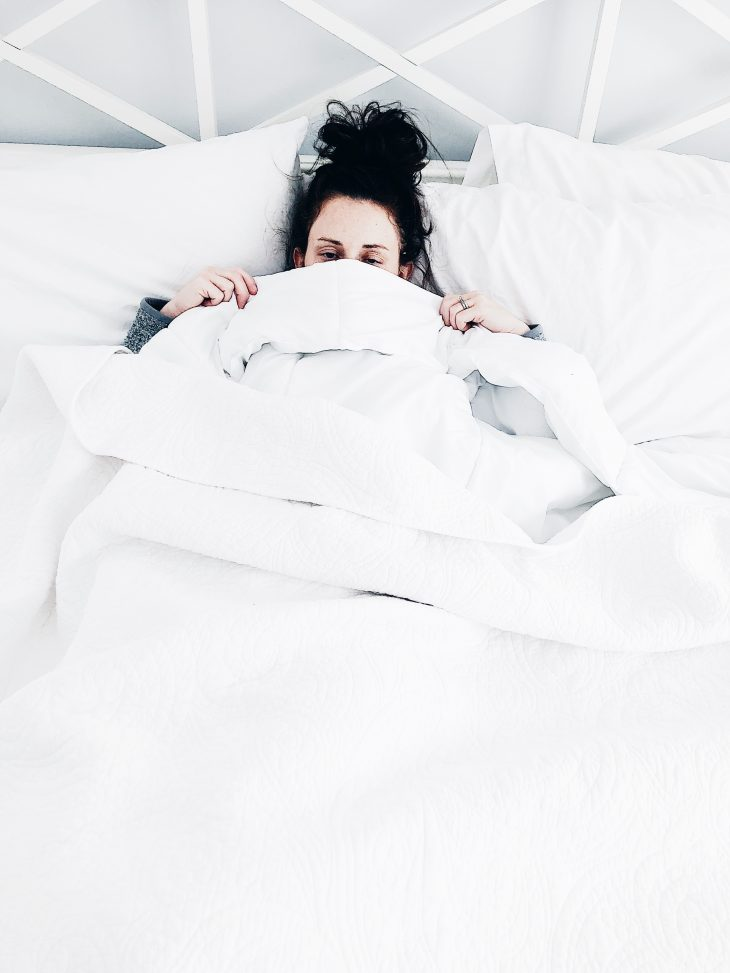 Brunette Woman Sick in Bed with White Comforters