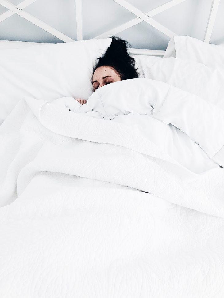 Woman Lying in Large White Bed Sleeping