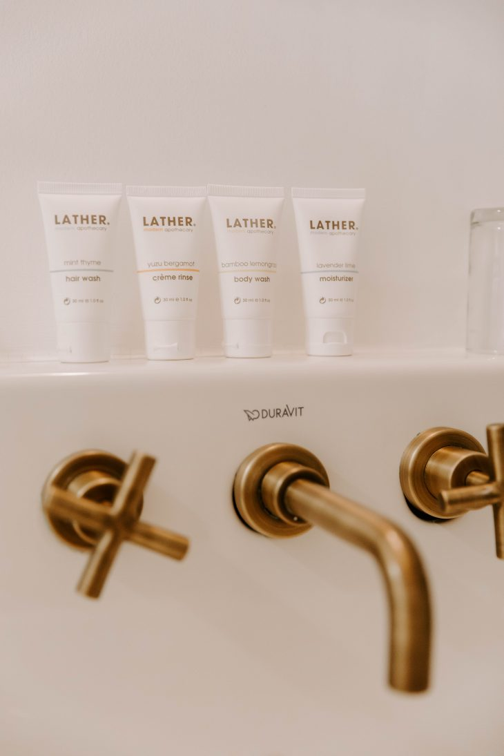 travel sized bath toiletries and bronze rubbed faucet