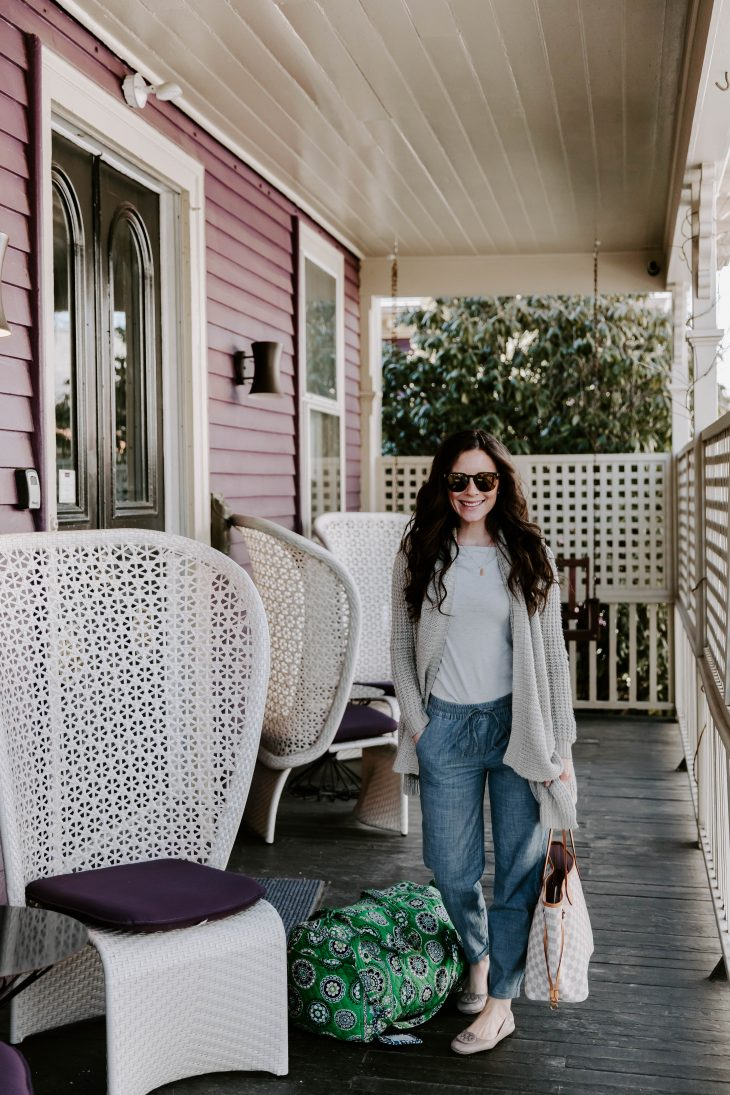 Woman wearing sunglasses, sweater, chambray pants with travel bag on purple porch of hotel in rhode island