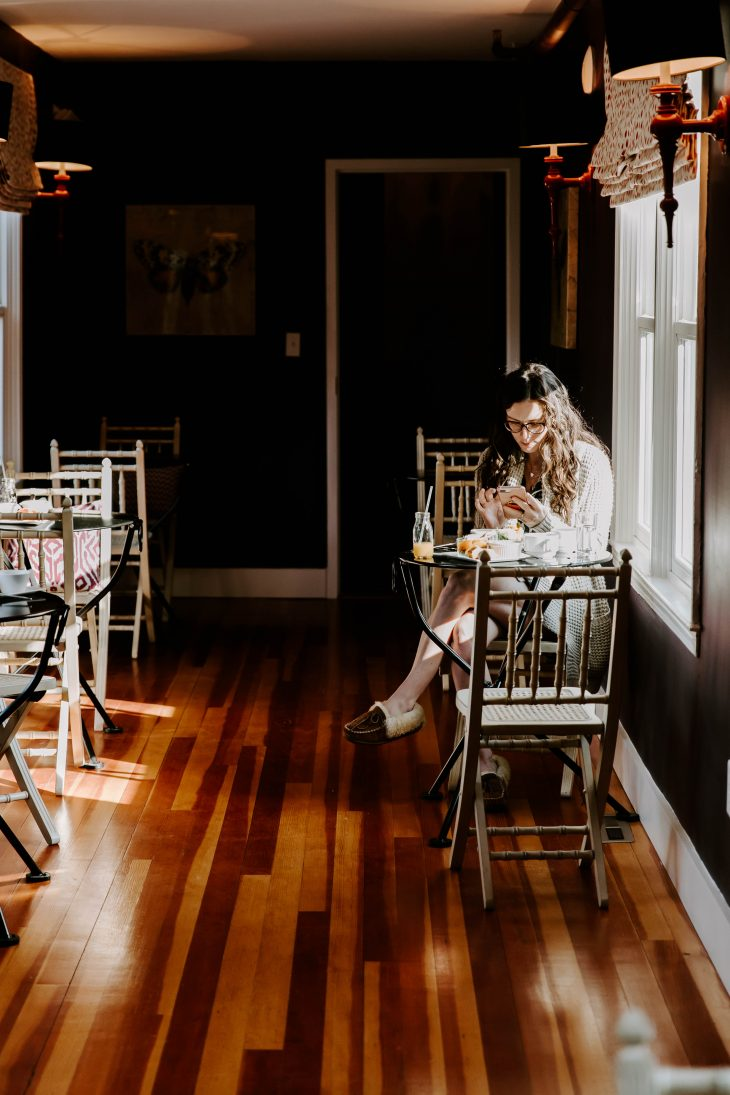 woman sitting in well lit room sipping coffee