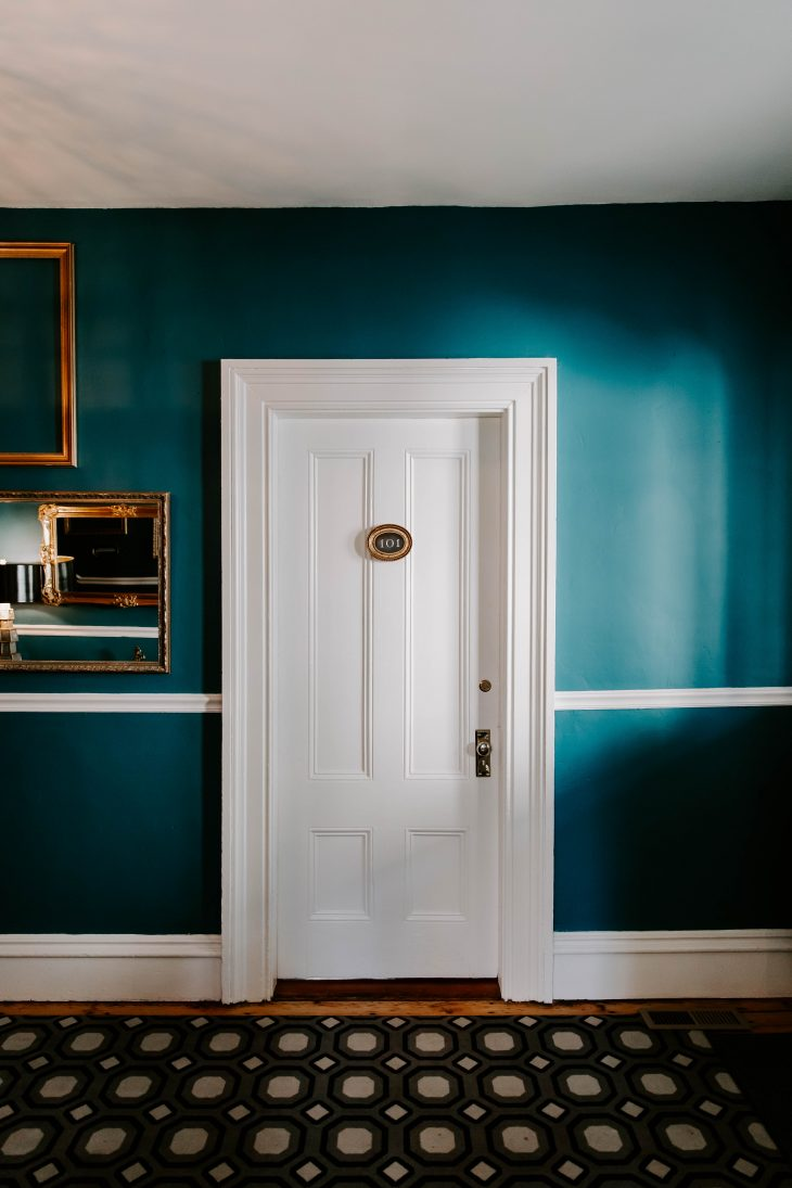 Teal wall gold picture frames white hotel room door