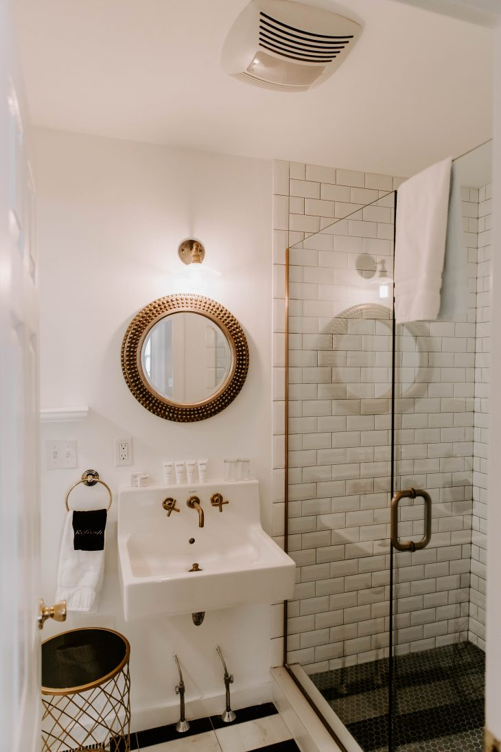 White bathroom subway tile shower gold mirror
