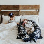 Sisters sleeping in hotel bed
