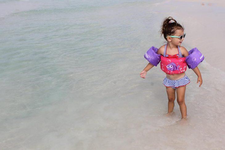 little girl wearing sunglasses on the beach