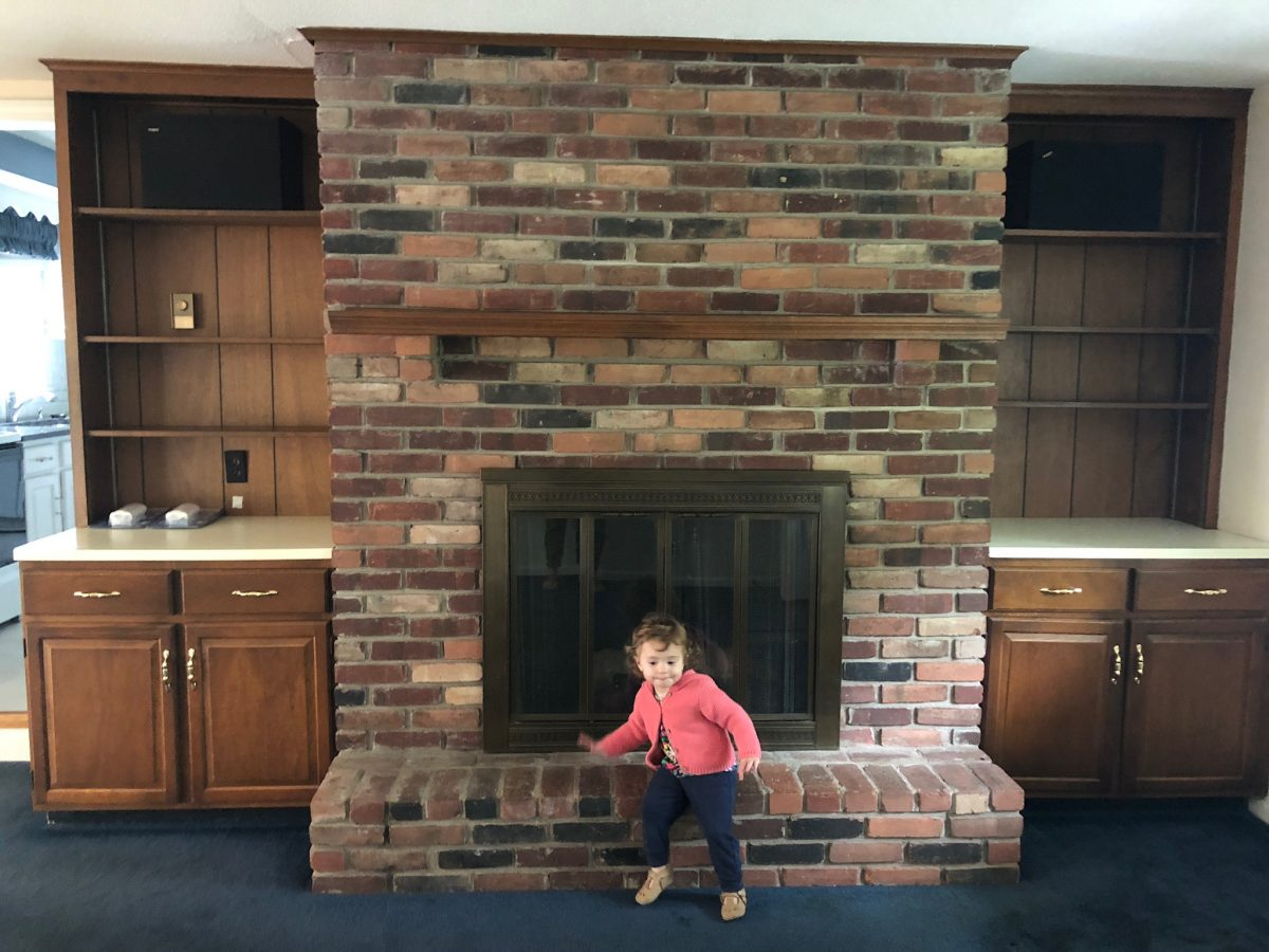 dark brick fireplace and wood built ins before whitewash