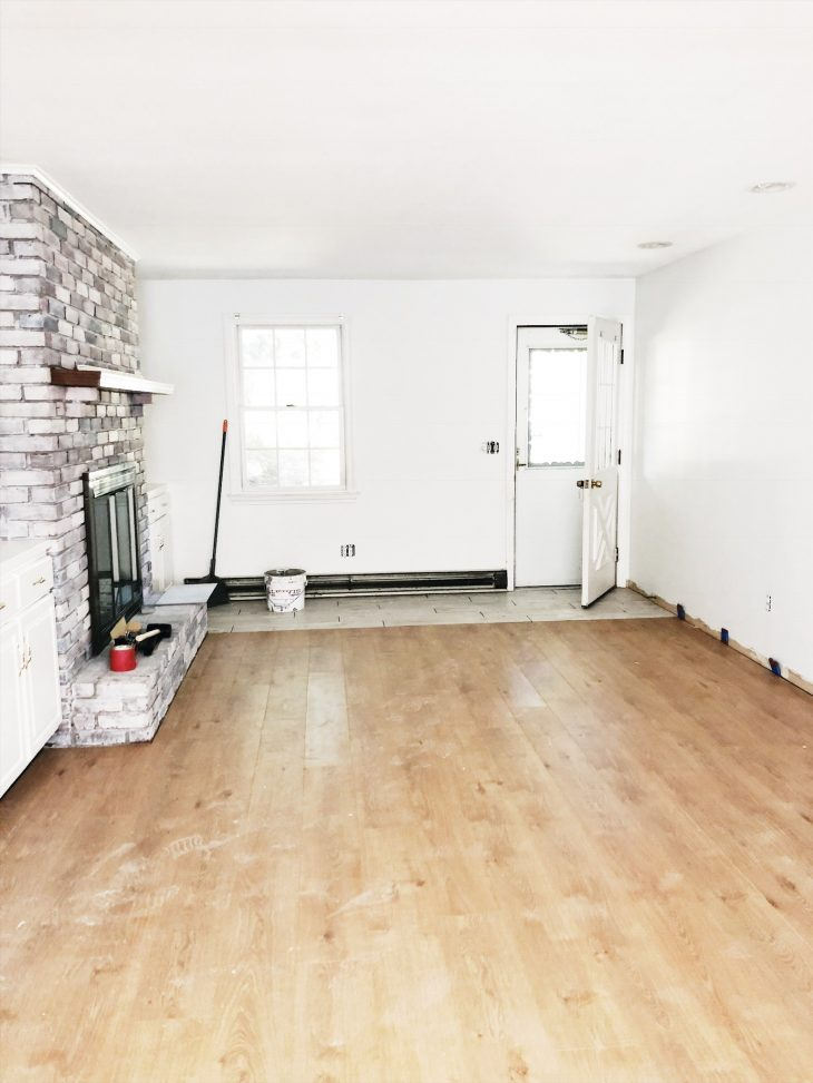 Family room with fireplace painted white and white oak flooring