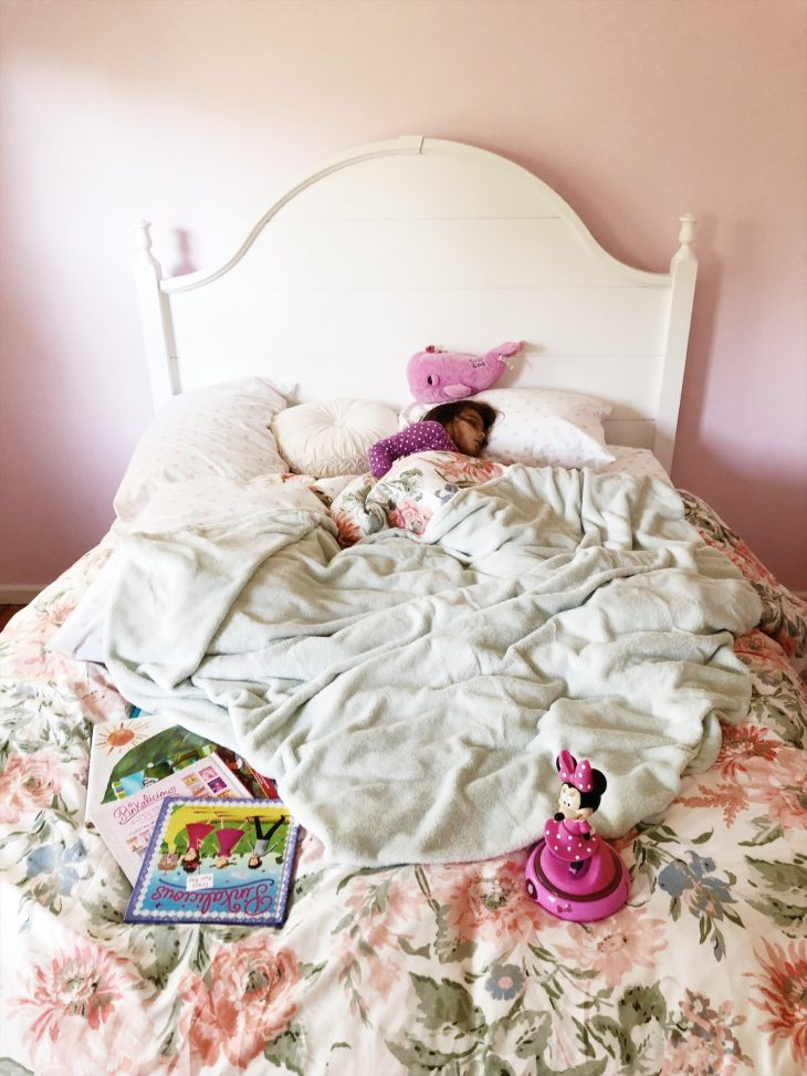 Girl sleeping with books in her bed
