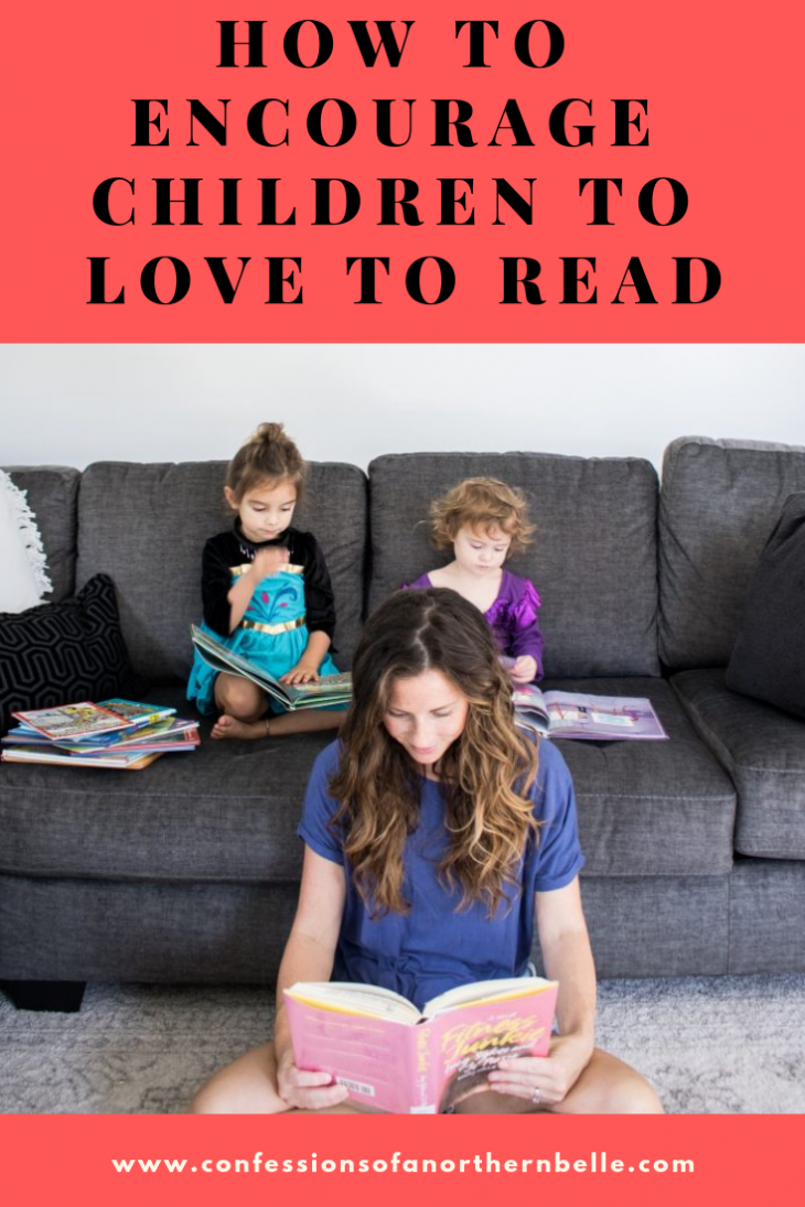 Two Girls Sitting on a Couch Reading books while Mom sits on floor in front of the girls reading a book too