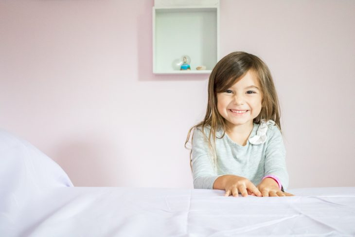 Little Girl standing bedside with purple sheets