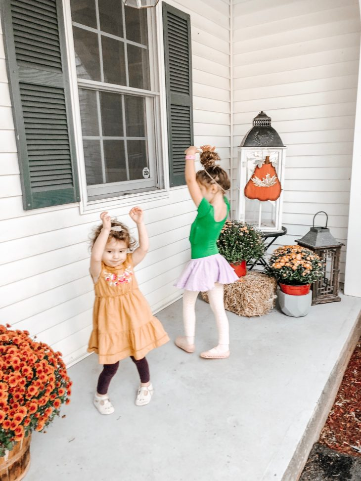 Sisters Twirling on the Front Porch Decorated for Fall