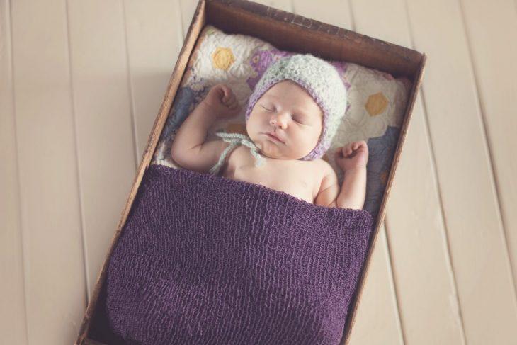 Newborn Sleeping in a Tiny Box