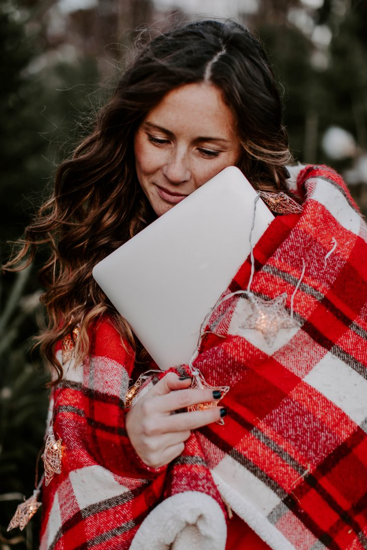 Woman wrapped in plaid blanket hugging laptop
