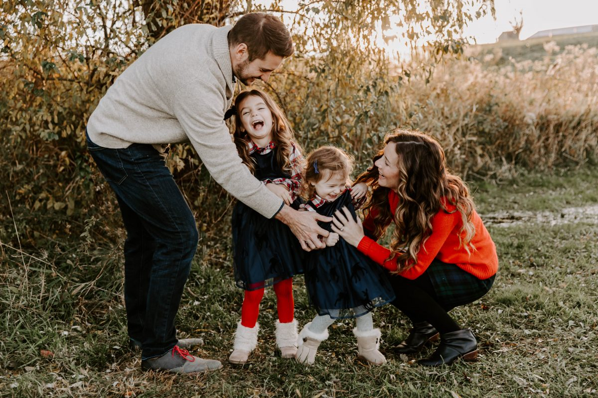 Man in Cream Sweater looking at youngest daughter wearing plaid shirt and navy dress. Child is in Mother's arms and another daughter stands between the parents looking up at them