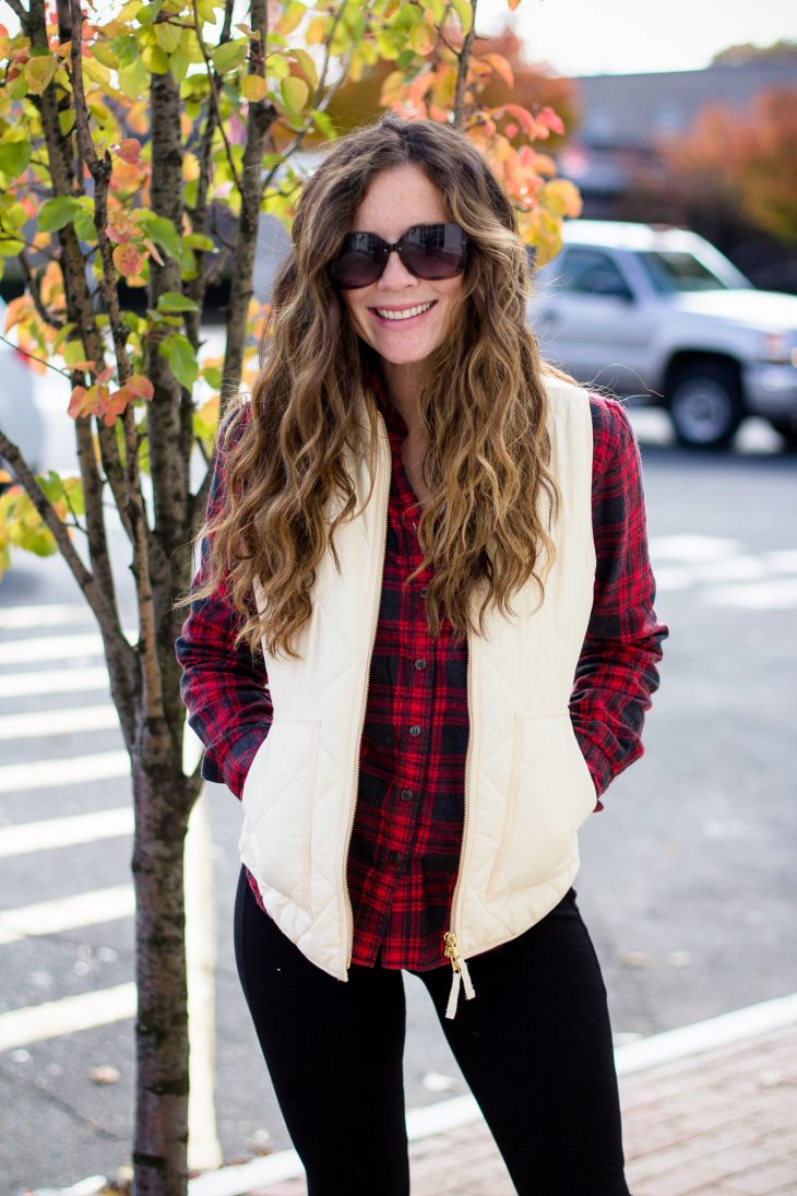 Woman with red and black jcrew flannel and white puffer vest