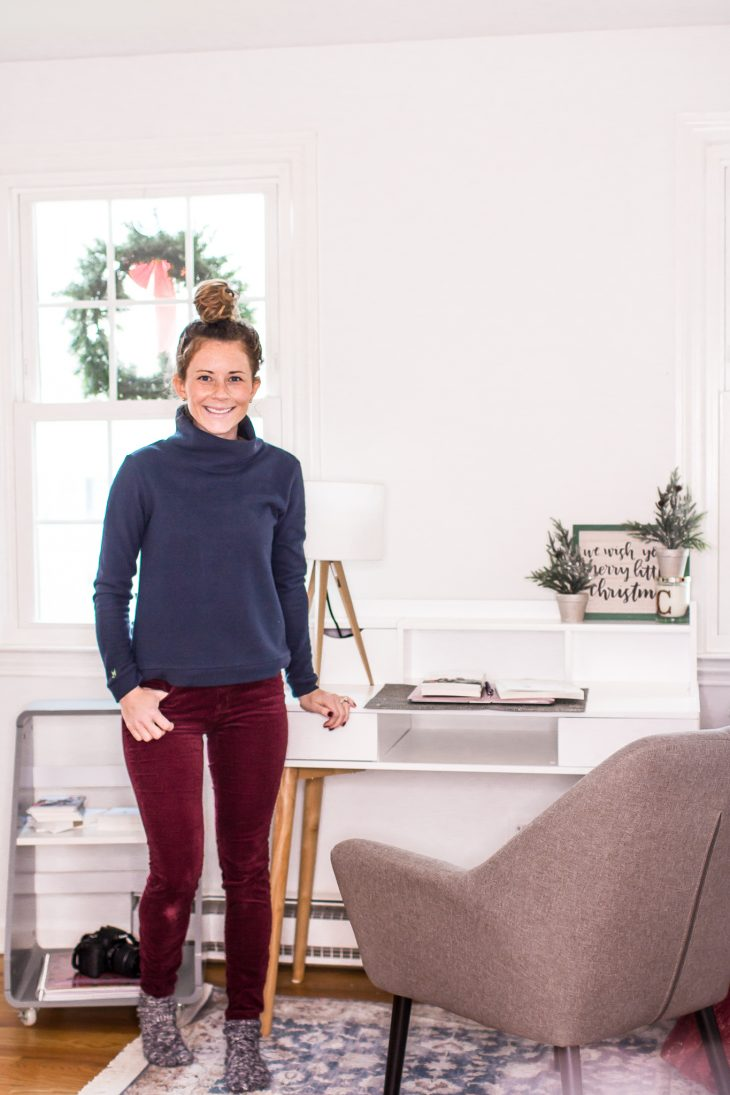 Woman Wearing Blue Turtleneck Maroon Pants Standing at White Desk