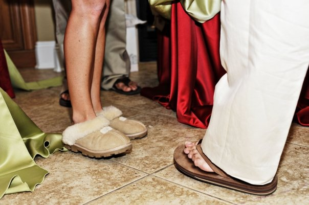 Foot photo of Woman wearing slide on furry slippers and man wearing khaki pants and brown sandals