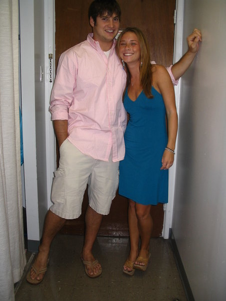 young man wearing pink shirt and khaki pants with arm around smiling young woman wearing a blue dress