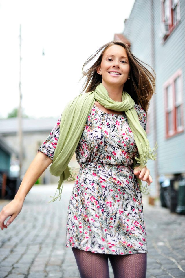 Young woman smiling while running, wearing a green scarf, floral dress, and purple tights