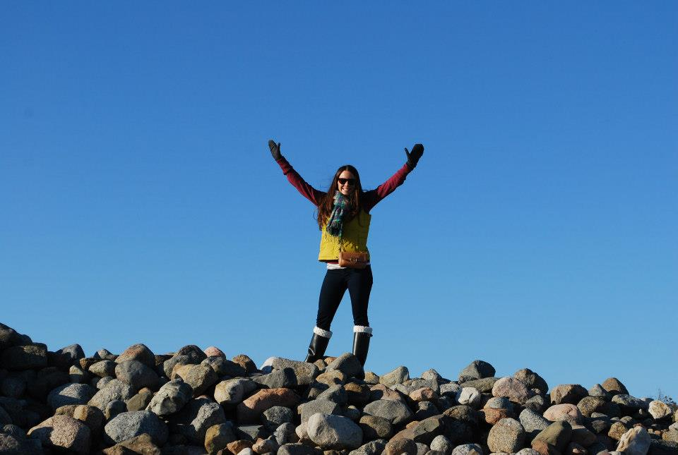 Woman wearing vest, scarf, gloves and boots with arms raised and smiling as she is standing on top of rock pile in Norway