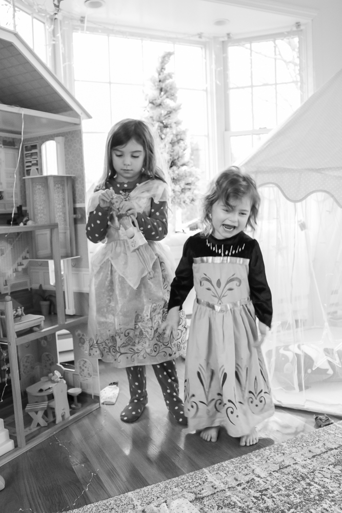 Black and white photo of two little girls standing side by side in princess dresses