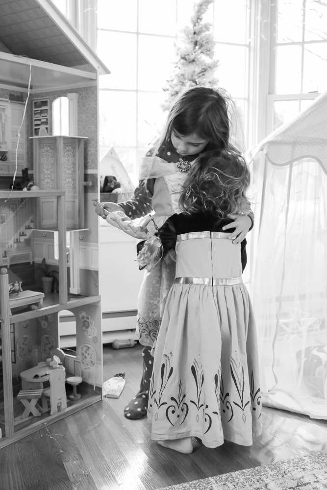 black and white photo of children hugging beside a large doll house