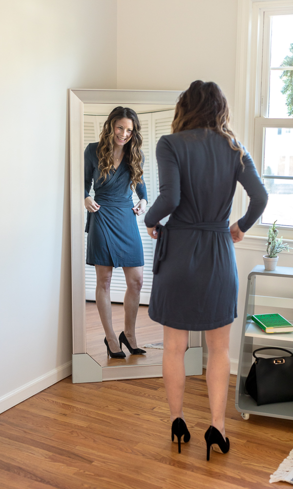 Woman wearing blue wrap dress and black high heels smiling at self in mirror