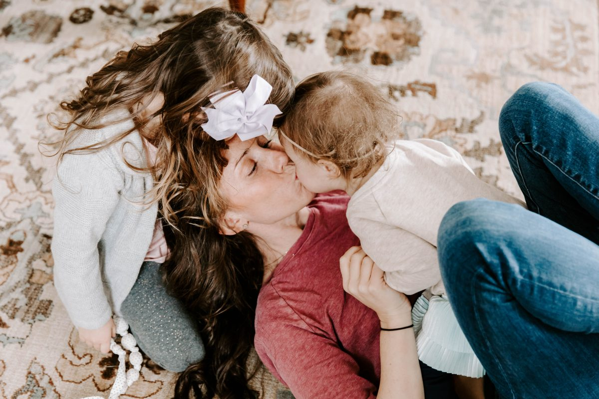 Mom kissing baby and toddler kissing mom on the head