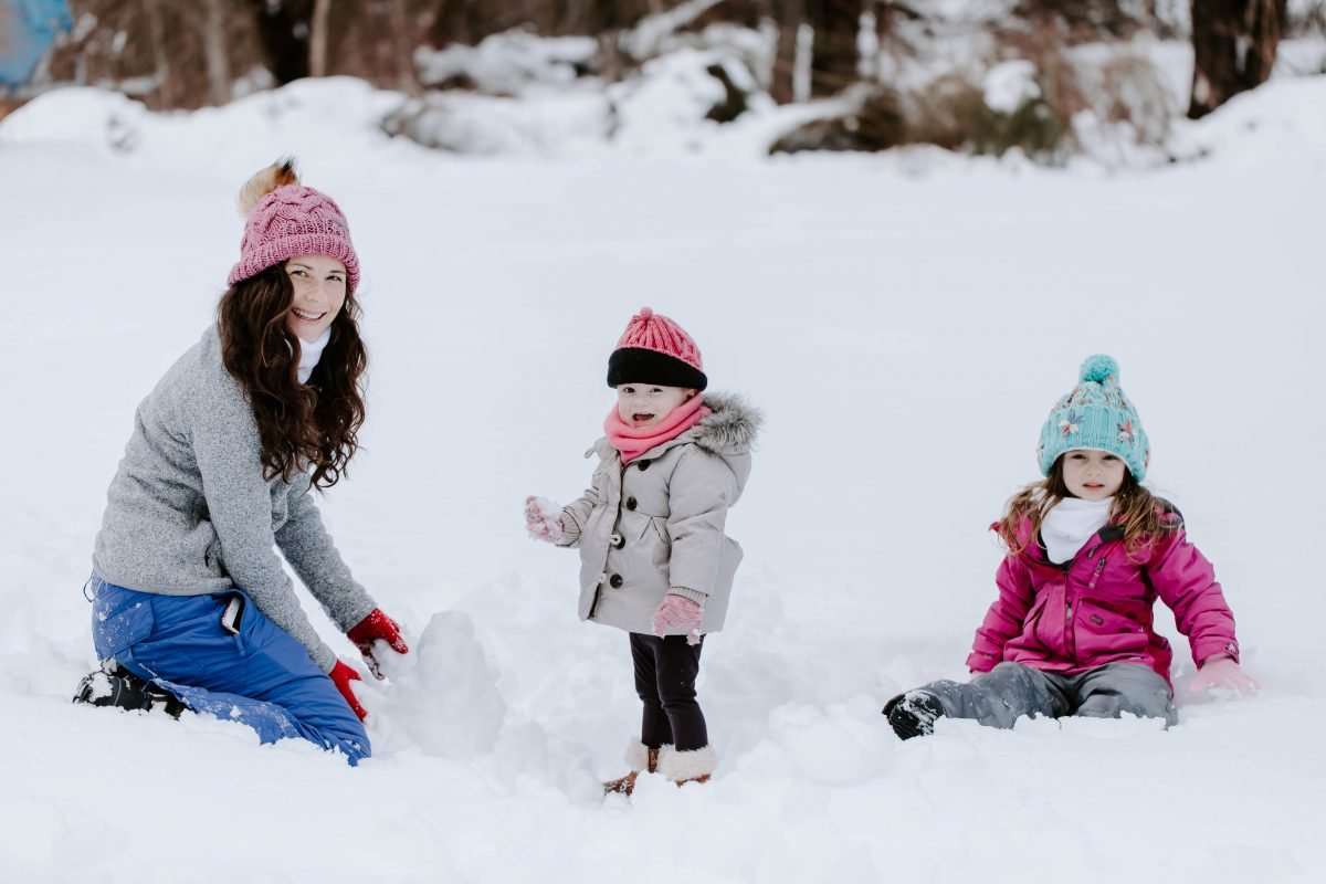 Woman wearing pink hat and winter clothes in the snow with little daughters wearing winter clothes in the snow