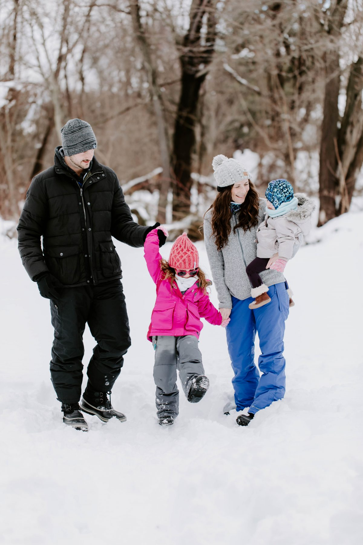 Family of four wearing snow pants and snow jackets, holding hands, laughing, and standing in the snow, Mom is holding Baby.
